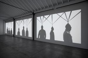 Controllo del corpo di Paolo Grassino, alla mostra Percorso in tre atti. Videoproiezioni, dvd, 3 canali con sonoro. Museo Pecci di Milano. 2012.Foto ZepStudio
